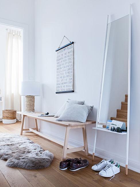 Minimalistyczny przedpokój z drewnianą ławką w stylu skandynawskim, białym stojącym lustrem i futrzanym dywanikiem
