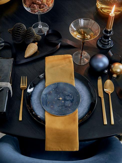Czarny stół z czarno - niebieską zastawą. złotą serwetką oraz złotymi sztćcami
