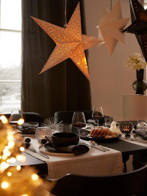 Czarny, prostokątny stół z czarną zastawą, szary bieżnikiem oraz gwiazdą wiszącą jako dekoracja
