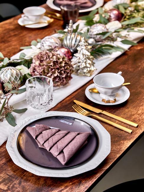 Drewniany stół z biały bieżnikiam, girlandą na środku, białymi i fioletowymi talerzami oraz złotymi sztućcami