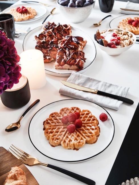 Esstisch mit verschiedenen süßen Gerichten wie Waffeln