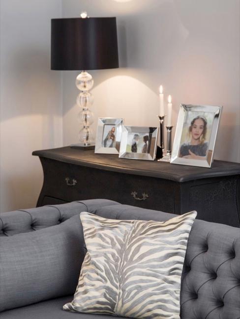 Sofá gris y cómoda negra con fotografías y lámpara de estilo Barroco