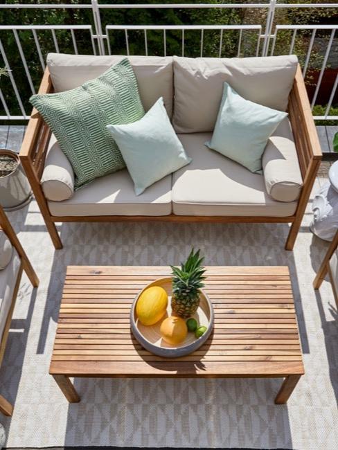 Sonniger Balkon mit Outdoormöbeln aus Holz, Balkonpflanzen und Deko Accessoires