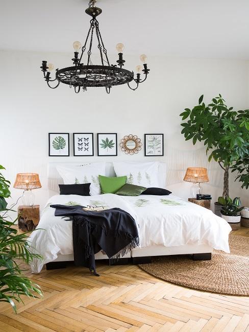 Schlafzimmer mit großem Bett, darüber eine Wandcollage und ein schwarzer Kronleuchter