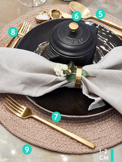 Close-up: zwarte serviesset met goudkleurige bestekset