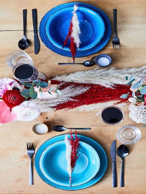 Gedekte tafel met blauwe borden, bestek en glazen
