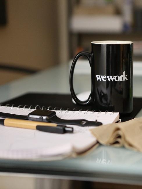 """Schreibtisch mit schwarzer Tasse mit der Aufschrift """"We work"""" neben einem Block und Stiften"""