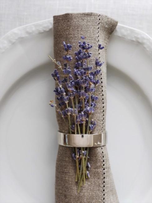 Plato blanco con servilleta marrón con anillo dorado y ramas de lavanda