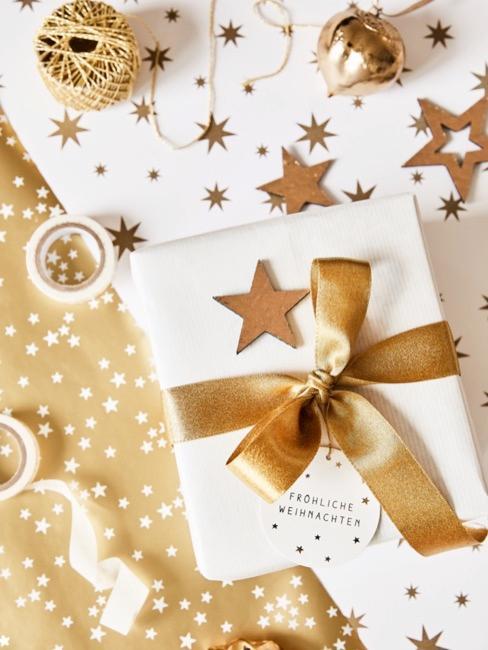 Regalo con papel blanco y materiales dorados con etiqueta de regalo