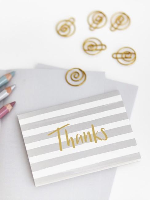 tarjeta de agradecimiento a rayas con una inscripción dorada