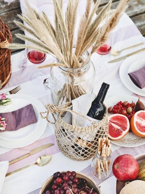 una mesa decorada con un jarrón,frutas y una cesta con vino tinto