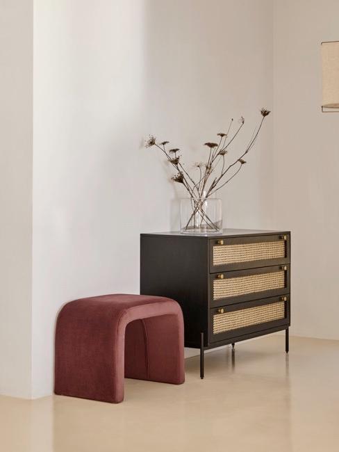 Pasillo minimalista con taburete de color burdeos, cómoda y flor encima