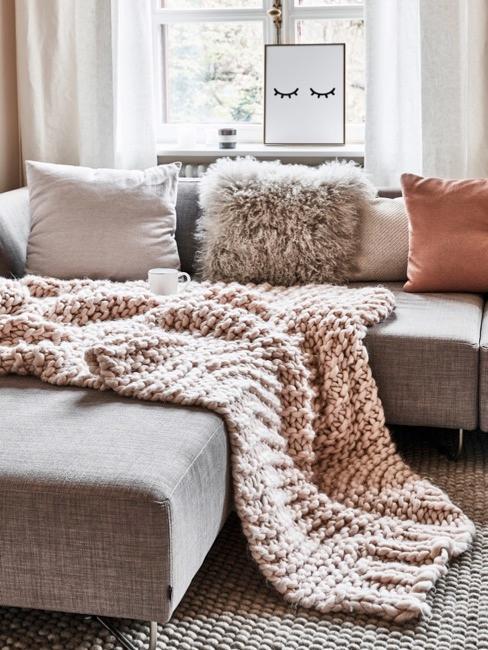 Sofá chunky knit con manta rosa y cojines distintos