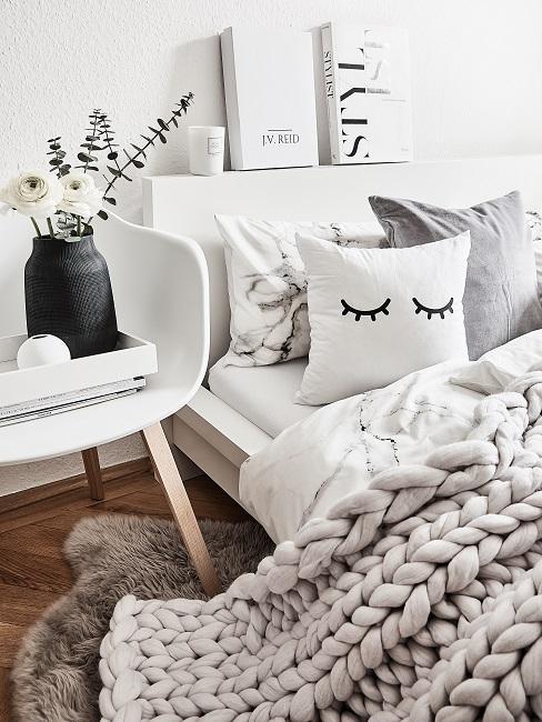 Bett mit kuscheliger Strickdecke, Kissen, Deko auf dem Bettkopf und dem Stuhl daneben