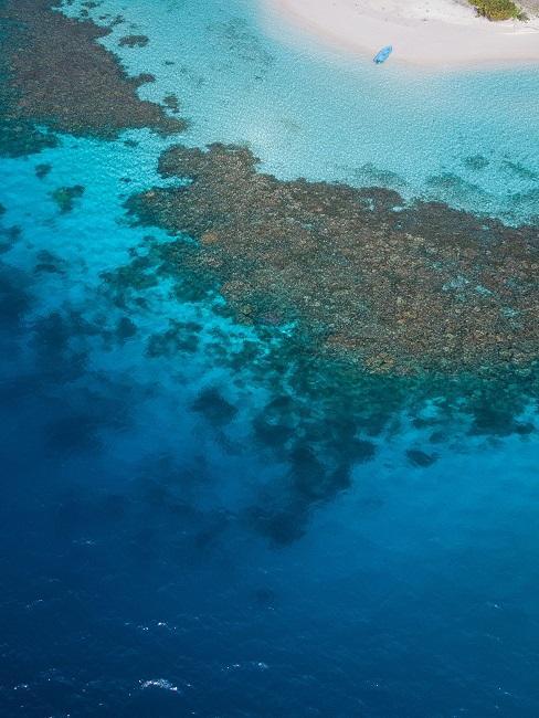Ein Riff mit Strand und blauem Wasser.