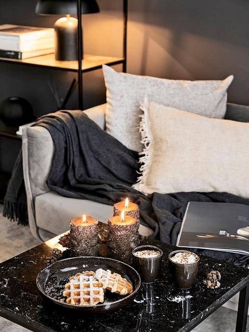 Gemütliches Wohnzimmer mit schwarzen, brennenden Kerzen.