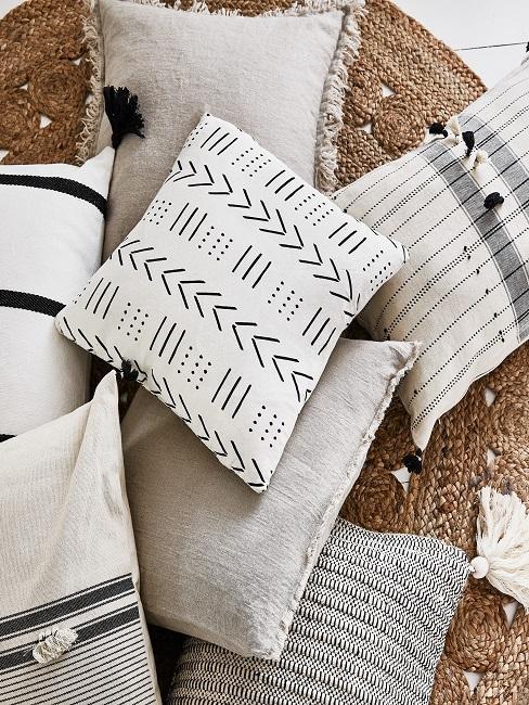 Viele helle Boho Kissen, teilweise mit Muster, liegen übereinander auf einem Jute Teppich