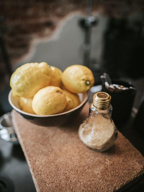 Mesa de corcho con azucarero en forma de bombilla y limones