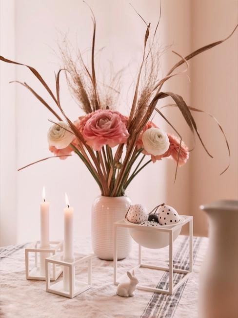 Mesa de Semana Santa con jarrón con flores en tonos rosados, velas y huevos de pascua