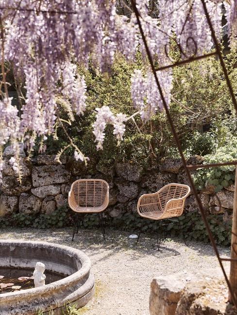 Korbstühle um einen Brunnen im Garten