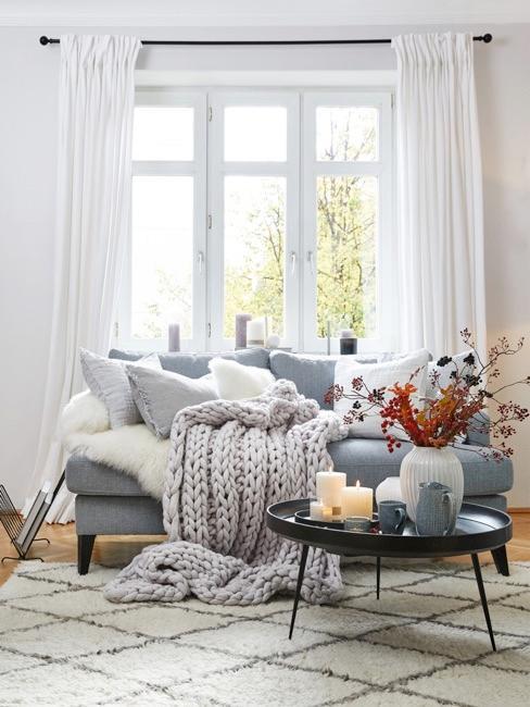 salon con un sofa cama con cojines y manta de punto