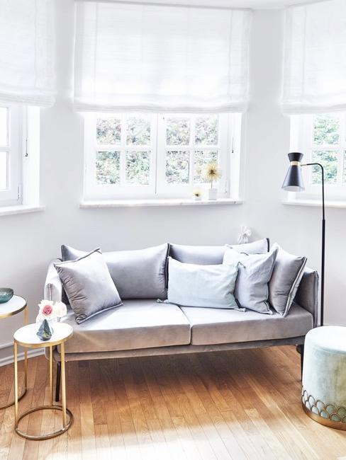 habitación con ventanas grandes, sofá de coor azul claro con cojines, un puf y lámpara de pie