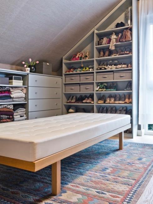 Ordentliches Ankleidezimmer mit Schrank, Regalen, Kommode und Sitzbank in Grau