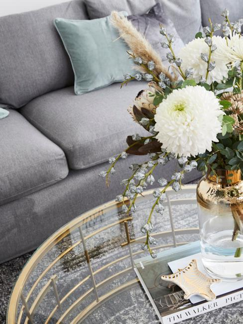 Nahaufnahme goldener Couchtisch mit Blumendeko in goldene Scandi Vase