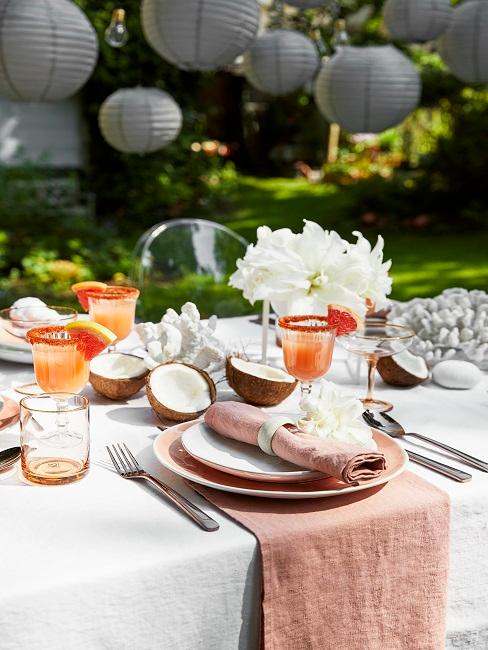 Gedeckter Tisch im Garten mit Lampions und sommerlicher Tischdeko