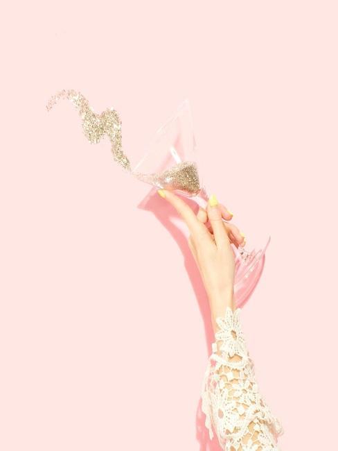 Frauenhand mit Martiniglas in der Hand, aus dem goldener Glitzer kommt