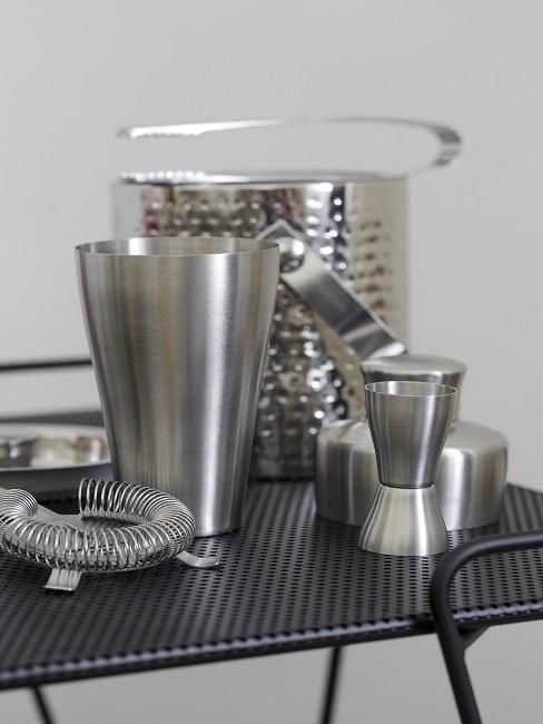 Silberfarbener Cocktail-Shaker auf einem schwarzen Barwagen mit passendem Zubehör