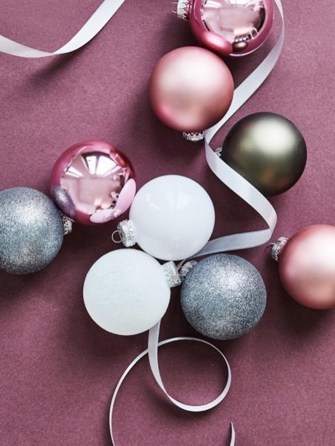 Set de bolas de Navidad en tonos rosas, grises y blanco sobre fondo rosa