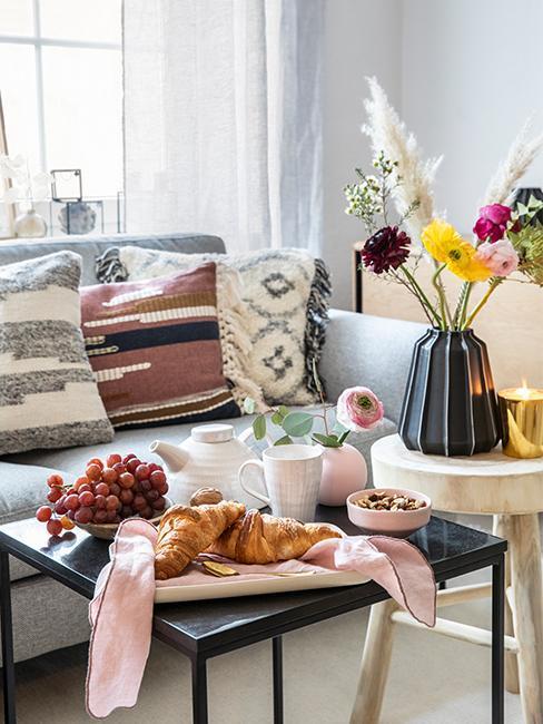 Nahaufnahme Couchtisch mit Frühstücksbrett, Obst und Deko Vasen