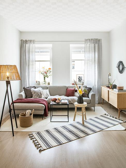Wohnzimmer mit grauer Couch und dunkelroter Textildeko