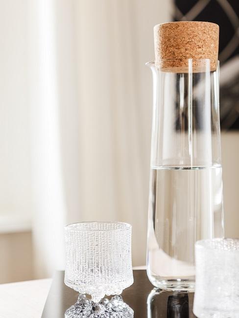 Wasserflasche mit Korken neben zwei Gläsern auf einem Tisch