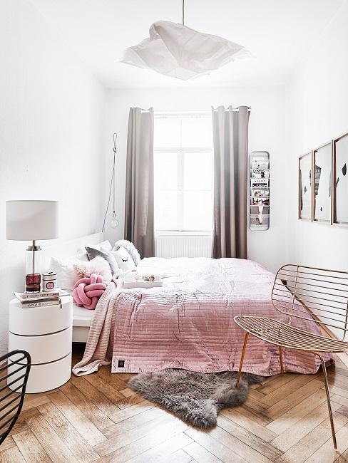Bett mit rosafarbenem Bettüberwurf vor einem Fenster, eine Wand mit Gallery Wall