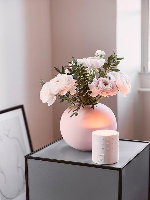 Owalny, biały wazon a w nim kompozycja z jaskrów, obok świeca dekoracyjna.