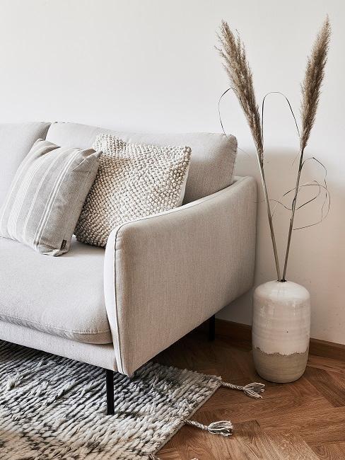 Ceramiczny wazon z trawą ozdobną, obok jasnoszara sofa.