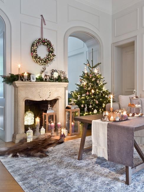 Gemütliches Wohnzimmer mit gedecktem Tisch auf eiem Teppich und Kamin, dazu viel Weihnachtsdeko wie ein Kranz und ein geschmückter Baum