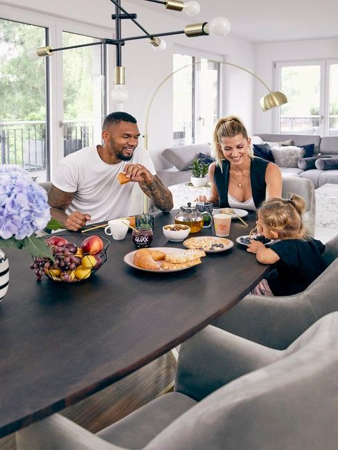 Team Harrison mit Tochter an dem Esstisch in Ihrem hellen Wohn- Essbereich
