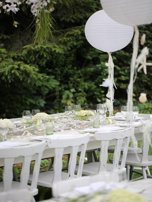 Eine lange weiße Tischtafel mit Blumengesteck als Tischdeko