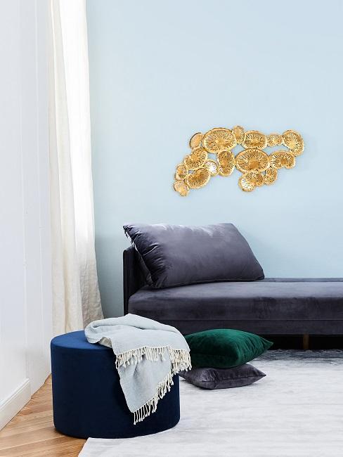 Babyblaue Wandfarbe hinter grauem Sofa und blauem Pouf