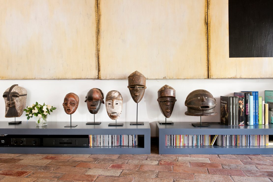 In the living room a low sideboard houses the stereo and African masks