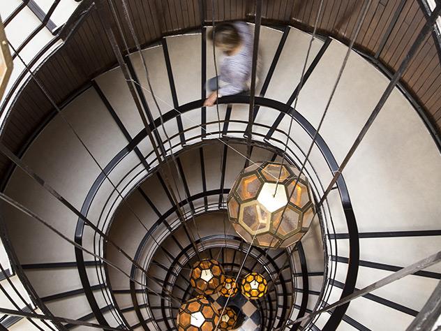 La escalera caracol está adornada con lámparas de estilo modernista
