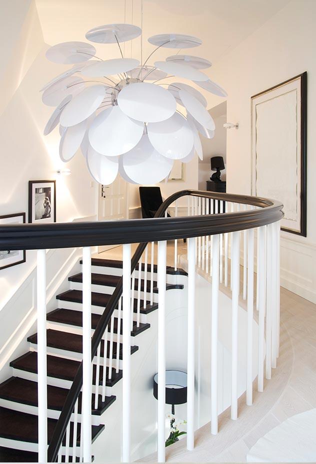 Una escultórica lámpara de diseño corona el fin de la escalera.