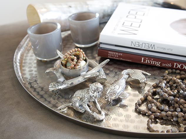Las bandejas de metal son perfectas para destacar libros, velas y esculturas decorativas.
