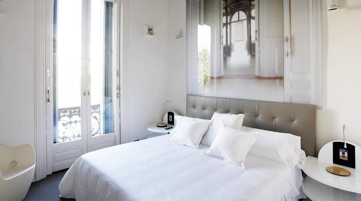Las camas de esta suite cuentan con un cabecero creado por fotografías de gran formato con detalles y perspectivas arquitectónicas del propio edificio.