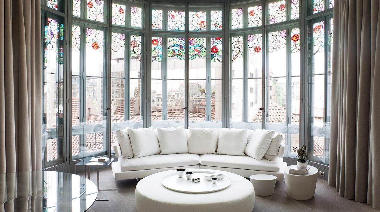 Esta suite del hotel ofrece vistas al Convent de Pompeia y a la montaña del Tibidabo a través de una vidriera modernista de forma semicircular con decoraciones florales de colores.