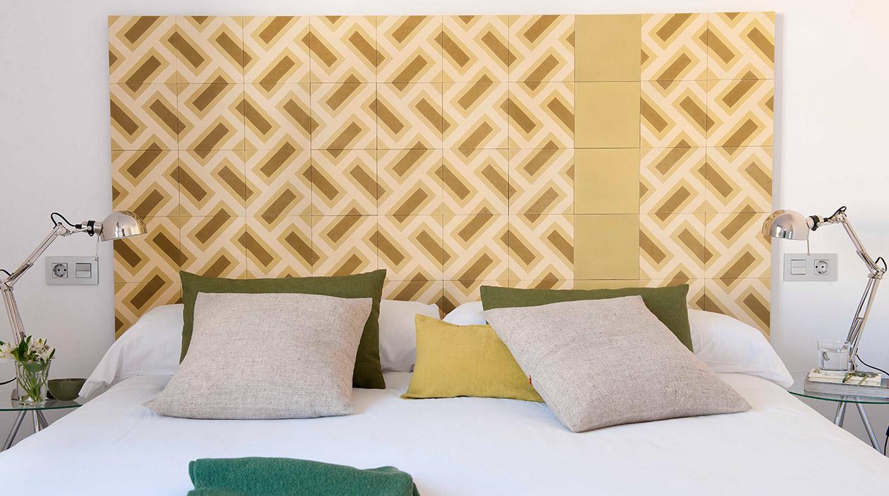 Todas las camas de los dormitorios están presididas por coloridos murales realizados con baldosas hidráulicas.