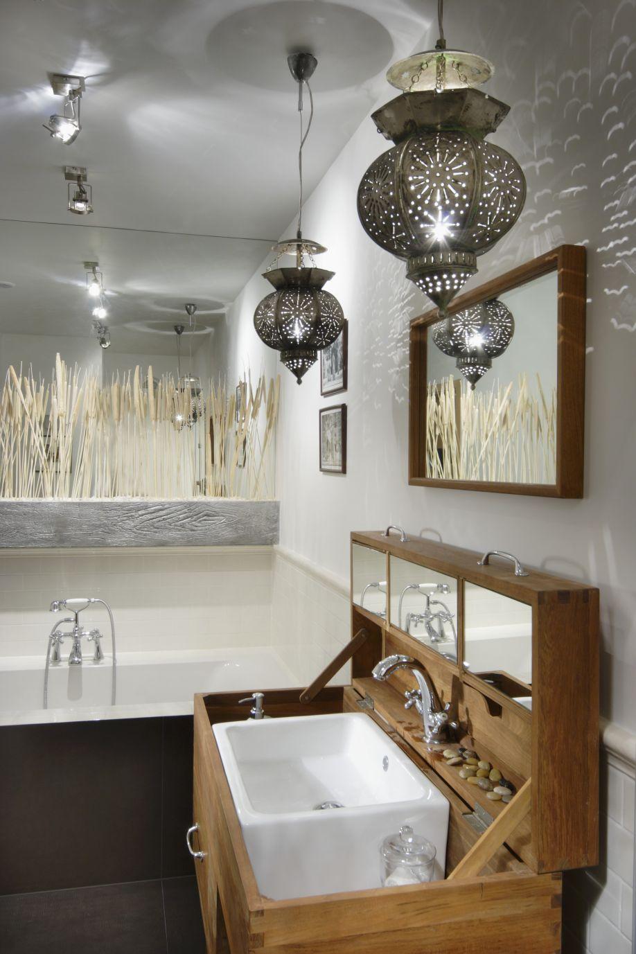 Orientalische Pendelleuchten über massgefertigter Waschtruhe mit Deckel; Spiegelfront mit Gräserverzierung über Wanne im Hinterg
